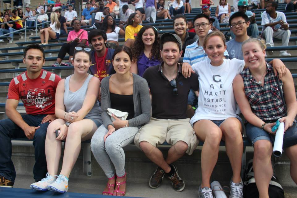 International students gather with a RMU Global Ambassador while bonding at a football scrimmage.