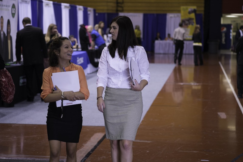 Two students walk through the various stands at the career fair.
