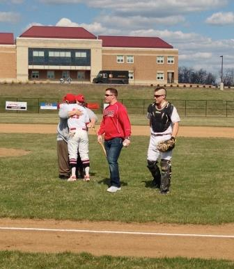 The team's catchers and chosen honorary pitcher share a moment after the opening ceremony is complete