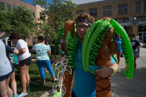 Student with two inflatable palm trees at the Beach Bash.