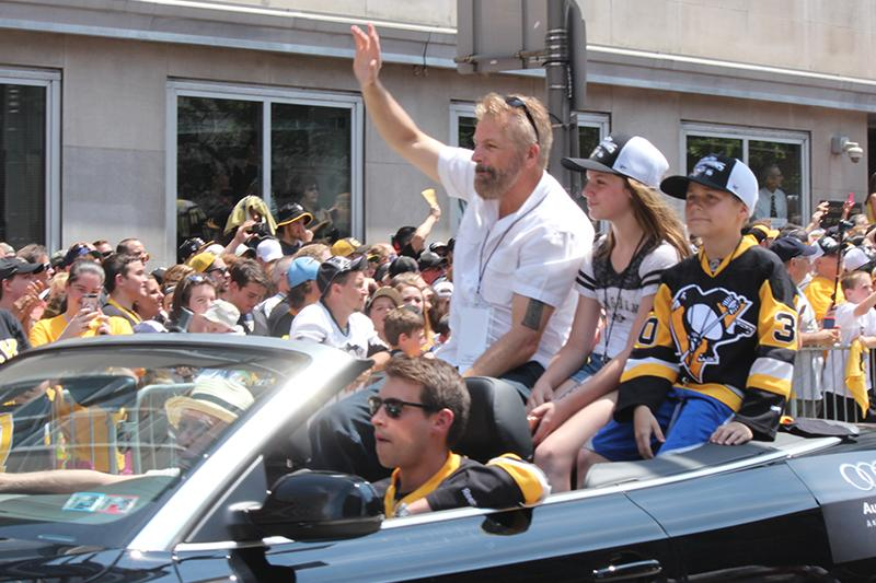 Radio analyst and former Penguin, Phil Bourque, waves to the crowd of Penguins fans.