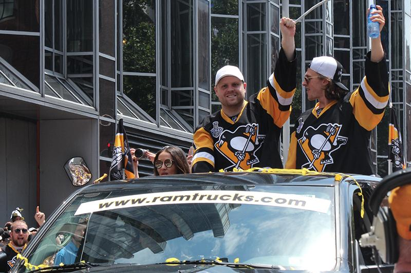 Phil Kessel (81) and Carl Hagelin (62) waves to the crowd as they ride down the Boulevard of the Allies.