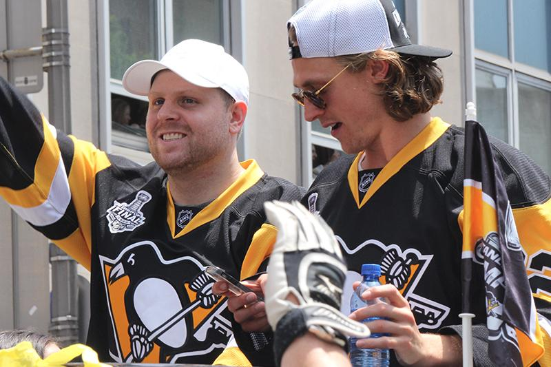 Phil Kessel waves to the crowd as Carl Hagelin (62) prepares to film the crowd.