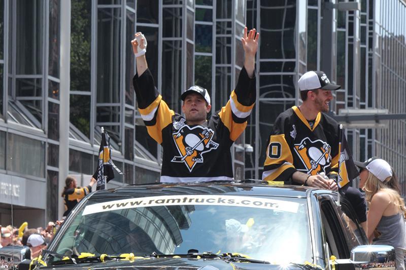 Bryan Rust (17) celebrates as Matt Murray (30) looks into a crowd of Penguins fans.