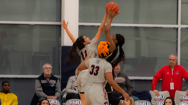 Natalie Villaflor goes for the block while Nneka Ezeigbo stands by against Wagner. Moon Twp, PA. (RMU Sentry Media/Michael Sciulli)