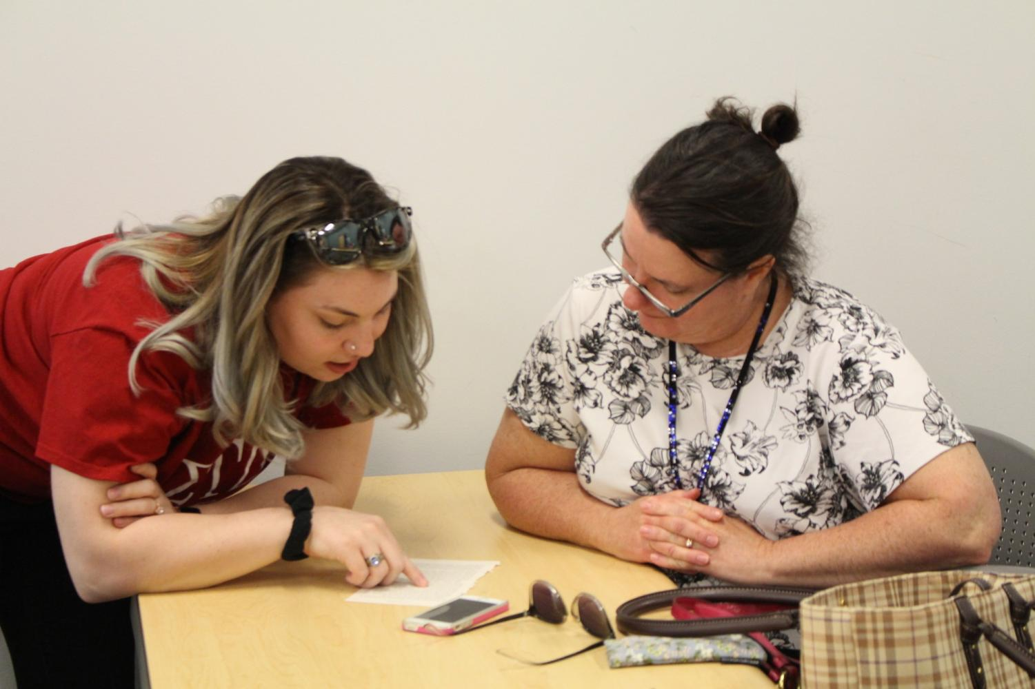 Sigma Tau Delta's Celia Smith shows an attendee how to do blackout poetry. Moon, PA. April 18, 2019. RMU Sentry Media/Garret Roberts. Photo credit: Garret Roberts Photo credit: Garret Roberts