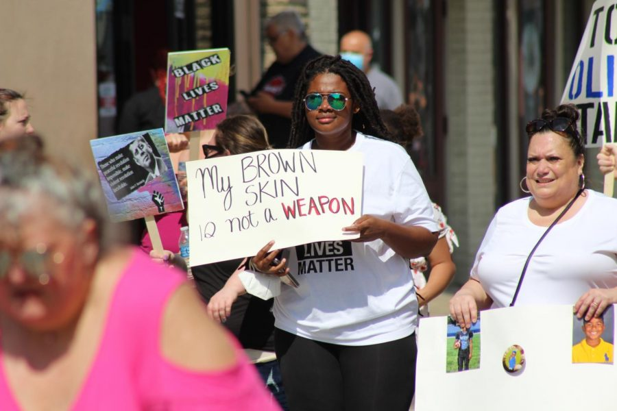 A marching protester carries a sign reading